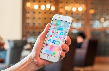 Persona sostiene un teléfono en su mano, en el que se ve la carpeta 'social media'.
