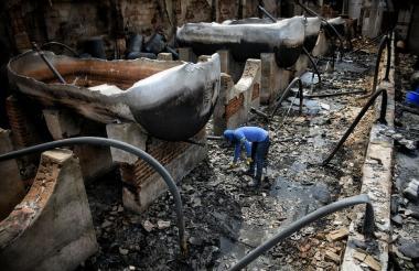 Un empleado ayuda a limpiar la zona del incendio.