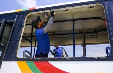 Dos hombres cambian los vidrios de un bus de Transmetro apedreado.