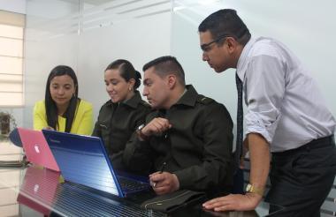 Policías y civiles revisan información en computadores portátiles.