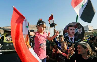 Ciudadanos sirios agitan la bandera nacional y las imágenes del presidente Bashar al-Assad en la Plaza Omeya en Damasco, tras los ataques de Estados Unidos y sus aliados.