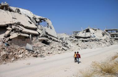 Dos escolares sirios pasan frente a edificios destruidos en una zona controlada por los rebeldes