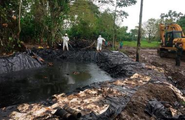 Trabajadores de Ecopetrol remueven restos del combustible derramado del pozo Lisama 158.