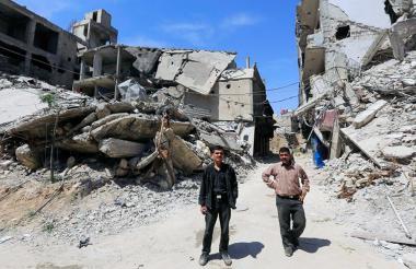 Dos sirios caminan por uno de los edificios destruidos en Damasco, tras los bombardeos de Estados Unidos y sus aliados Francia y Reino Unido.
