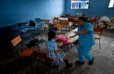 Una profesora y una estudiante en uno de los salones de clase que recibe poca ventilación y luz natural, en el colegio José Consuegra Higgins.