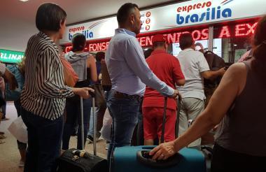 Un grupo de viajeros comprando tiquetes.
