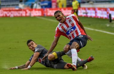 El lateral del Junior Gabriel Fuentes es derribado por el atacante Leonardo Castro en una dura falta.