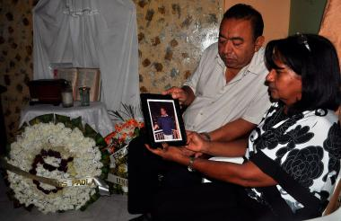 Los padres de Óscar Santís, Evelio Santís y Melvis Arismendy, desde la sala de su casa aprecian una fotografía de su hijo.