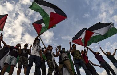 Manifestantes agitan banderas palestinas y gritan consignas frente a la embajada de Israel, durante una manifestación en el centro de Atenas.