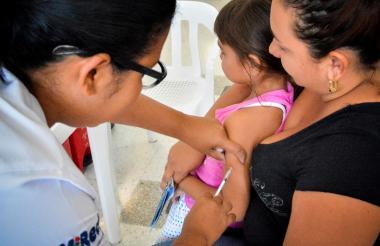 Menor recibe vacuna contra el sarampión.
