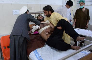 Familiares afganos mueven a una víctima a una cama mientras recibe tratamiento en un hospital después de múltiples explosiones dirigidas contra un estadio de cricket en Jalalabad.