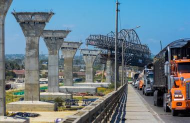 Varios vehículos transitan por el viejo puente Pumarejo. Al fondo se observa la construcción de la nueva estructura.