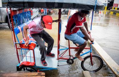 Miguel Martínez deja a un pasajero en el andén después de haberlo transportarlo en medio de la lluvia.
