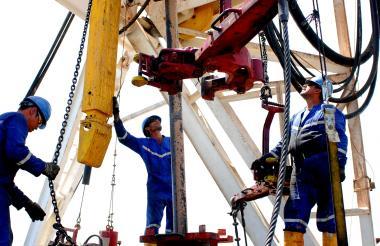 Trabajadores operan equipos de un campo petrolero en los llanos orientales.