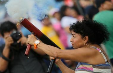 Una mujer dispara un mortero casero en una protesta.