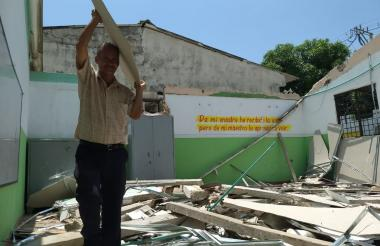 Un directivo retira una de las láminas del aula destruida.