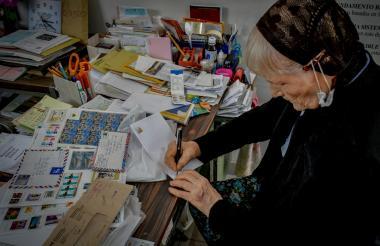 La canadiense Ruby Jean Campbell, radicada en Barranquilla, escribe en un sobre de carta los datos del remitente y destinación del manuscrito.
