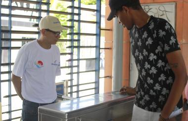 Un joven pasa la tarjeta de Transmetro en una estación ante la mirada de uno de los nuevos guías.