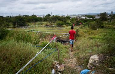 Un joven camina por las delimitaciones hechas por varios invasores en el barrio El Edén.