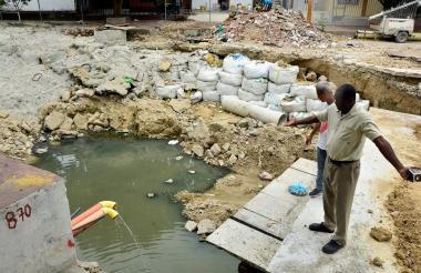 Robert Romaña y Alfonso Torres muestran el represamiento de aguas de alcantarilla.