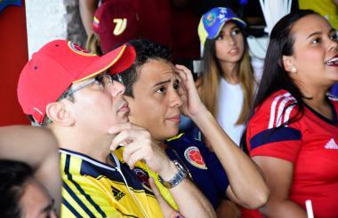 Espectadores ven por televisión un partido de fútbol de la Selección Colombia.