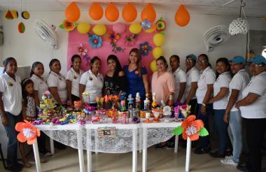 Las mujeres mostrando los productos elaborados con material reciclable.