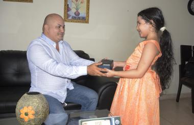 Una niña entrega el regalo a su padre, previa la celebración del 24 de junio.
