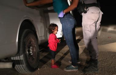 Una niña hondureña llora mientras la policía fronteriza requisa a su madre quien es solicitante de asilo.