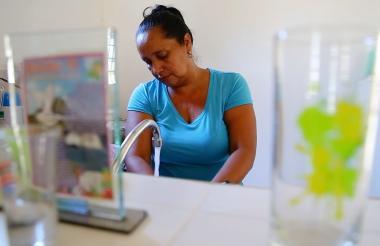 Una habitante del barrio El Bosque muestra cómo fue mejorada su cocina.