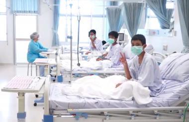 Los niños tailandeses posan para la cámara en medio de la reclusión en un centro médico.
