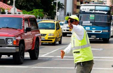 Un orientador regula el tránsito en una vía de la ciudad.