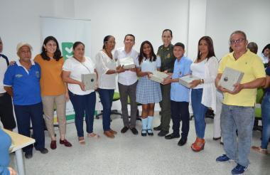 Grupo de estudiantes y profesores con funcionarios de la Oficina para la Seguridad y Convivencia Ciudadana y un representante de la Policía.