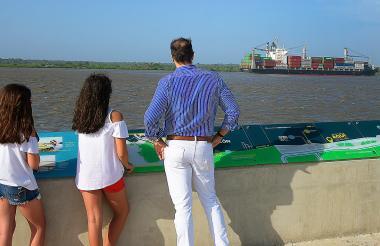 Cuatro visitantes del Gran Malecón del Río observan un barco que pasa por el río Magdalena.