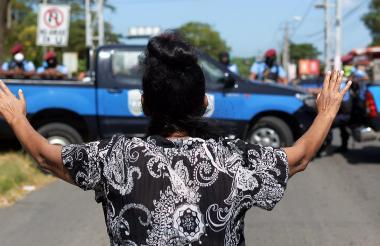 Una mujer gesticula mientras la policía monta guardia en los alrededores de la Catedral, en Managua.