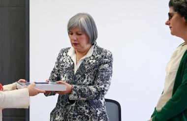 María Paulina Riveros (izq) entrega a Patricia Linares, presidenta de JEP, el informe sobre las Farc.