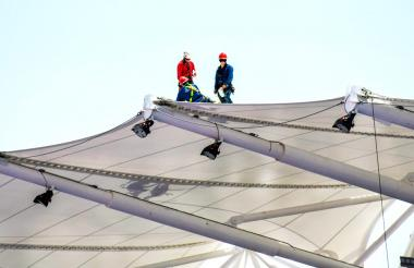 Tres obreros instalan la membrana arquitectónica (techo) de la gradería principal del Patinódromo.