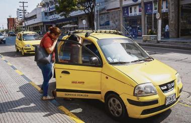 Una ciudadana solicita el servicio de taxis en Barranquilla, donde circulan 17 mil de estos vehículos de servicio público, incluyendo el área metropolitana.