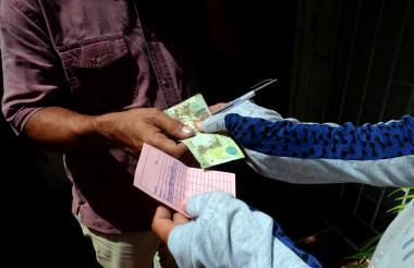 Un cliente paga a uno de los cobradores y este sostiene en su mano un cartón de registro de la ruta.