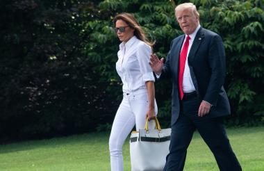 Donald Trump y su esposa Melania caminan en los jardines de la Casa Blanca.