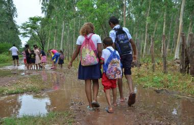 Niños de la vereda El Toco en momentos en que se dirigían a la escuela, sorteando en un camino lleno de agua y lodo, entre otro tipo de dificultades.