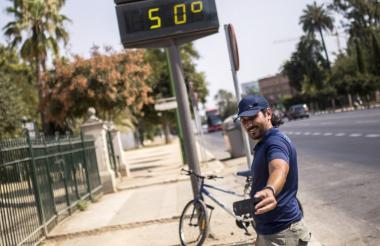 Un ciudadano se toma una selfie en Sevilla (España) teniendo de fondo un marcador que muestra 50 grados de temperatura este sábado.