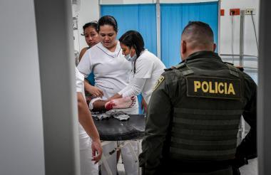 Personal médico atiende a un paciente que ingresó con herida a bala, mientras un policía los vigila.