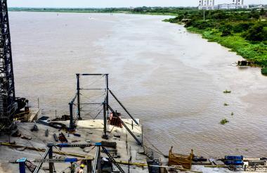 Ingenieros y técnicos de Triple A se acercan en una lancha a la draga que derramó el combustible en el río Magdalena.