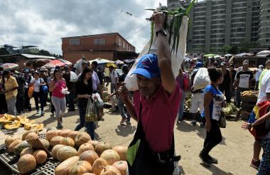 Antes de la emisión de nuevos billetes, venezolanos compran en el mercado de Coche en Caracas.