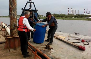 Funcionario de la CRA y Triple A mueven uno de los barriles de aceite extraídos del río Magdalena.