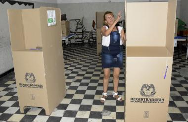 Una funcionaria de la Registraduría instala los cubículos en el puesto de votación que funcionará en el Codeba.