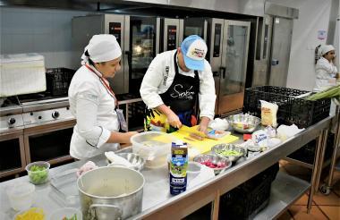 Dos chefs preparan alimentos en la cocina principal de la feria, el lugar desde donde se alistan los platos para los chefs invitados.