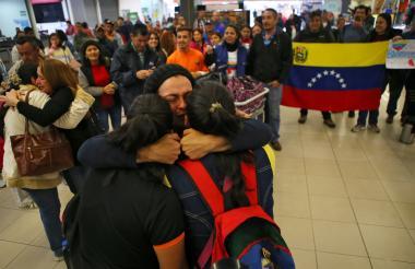 Los familiares venezolanos son abrazados por familiares a su arribo a la terminal de autobuses en el norte de Lima, después de viajar durante 20 horas desde Tumbes, al noroeste de Perú.