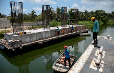 Los obreros de firma A Construir trabajan en las vigas del puente sobre el caño.