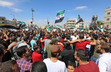 Ciudadanos sirios agitan la bandera de la oposición mientras se manifiestan contra el régimen y su aliado Rusia, en la ciudad de Idlib, controlada por los rebeldes.